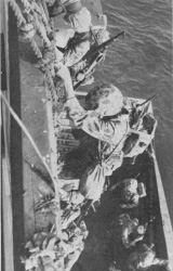 Troops climbing down cargo nets into landing craft