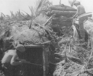 Photograph of wary Marines inspecting a Japanese bunker