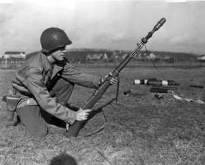 Photograph of soldier preparing to fire a rifle         grenade