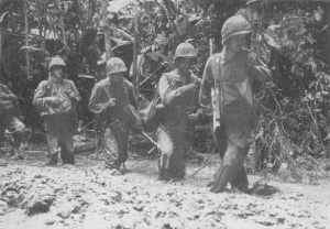 Photograph of infantry slogging through the mud