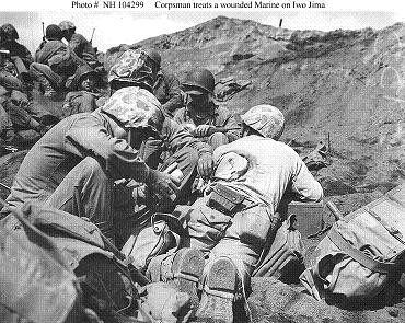 Photograph of corpsman treating a back wound