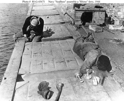 Photograph of Seabees assembling prefabricated pontoons