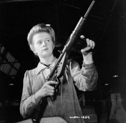 Photograph of factory worker with Sten submachine gun