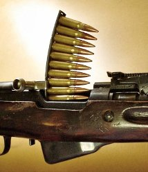 Ammunition being loaded into a rifle from a stripper clip